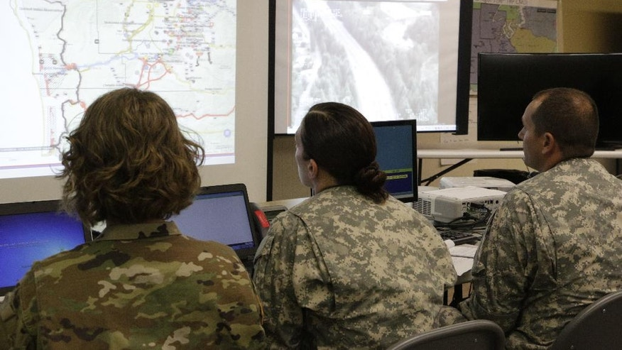 Members of the Washington National Guard look at screens showing a map of damage to roads following a simulated earthquake and tsunami, Thursday, June 9, 2016, in Shelton, Wash. Officials in the Pacific Northwest have been rehearsing scenarios on how the region would deal with a dual natural disaster that could kill thousands, cut off coastal communities, and collapse phone and internet service. (AP Photo/Rachel La Corte)