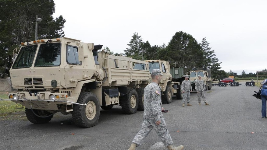 A member of the National Guard walks by a medium tactical vehicle that can be used for decontamination, on Thursday, June 9, 2016, in Shelton, Wash. Washington is participating in a multiday earthquake and tsunami readiness drill in the Pacific Northwest called Cascadia Rising. (AP Photo/Rachel La Corte)