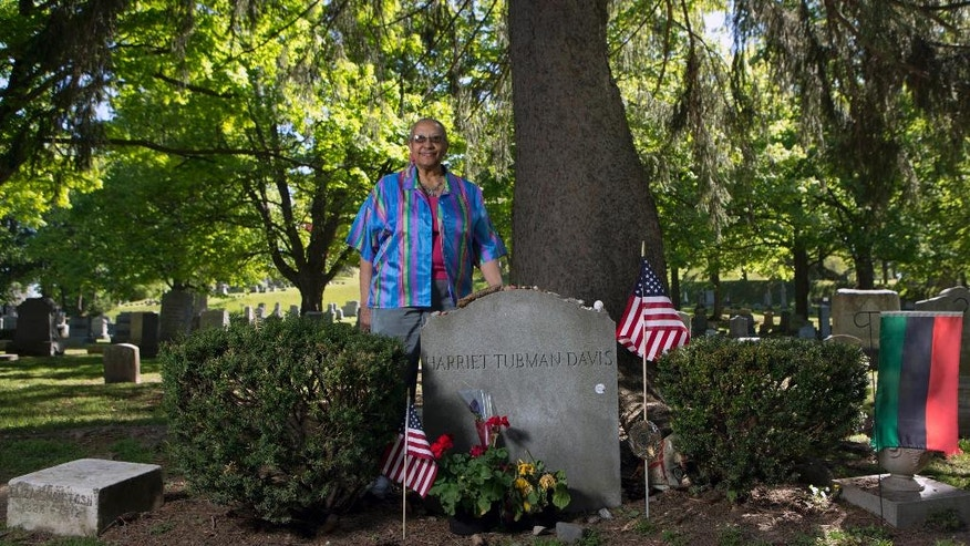 In this Thursday, May 19, 2016 photo, Judith Bryant, a great-great-grandniece of Harriet Tubman, poses at Tubman's grave site at Fort Hill Cemetery in Auburn, N.Y. Tubman's upcoming debut on the $20 bill is just half the good news in the upstate New York town where the Underground Railroad conductor settled down and grew old. Bryant's great-great grandfather was Tubman's brother, and was among the dozens of slaves she guided north to freedom. (AP Photo/Mike Groll)