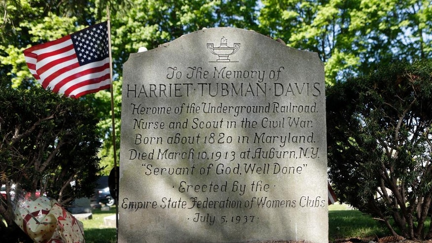 In this Thursday, May 19, 2016 photo, the inscription on Harriet Tubman's gravestone is seen at Fort Hill Cemetery in Auburn, N.Y. Tubman's upcoming debut on the $20 bill is just half the good news in the upstate New York town where the Underground Railroad conductor settled down and grew old. A long-sought national historical park here honoring Tubman could be officially established as early as this summer.  (AP Photo/Mike Groll)