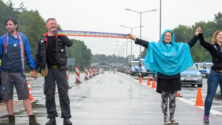 Peace activists form  a human chain on the street leading towards the US air base during the 'Stopp-Ramstein' campaign in Ramstein,  Germany, Saturday June 11, 2016. Demonstrators have formed a human chain near the  U.S. air base in western Germany to protest against lethal drone  strikes.  Protest organizers contend that the Ramstein Air Base is used to relay flight control data for lethal drone strikes. They are calling for the base, a major U.S. military hub, eventually to be closed altogether.   (Oliver Dietze/dpa via AP)