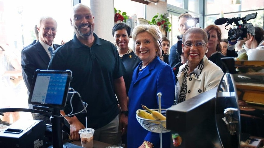 Democratic presidential candidate Hillary Clinton, joined by, from left, Washington City Council member Jack Evans, Uprising Muffin Company owner Donnie Simpson, Washington Mayor Muriel Bowser and Del. Eleanor Holmes Norton, D-D.C., pauses during a stop at the store in Washington, Friday, June 10, 2016. (AP Photo/Alex Brandon)