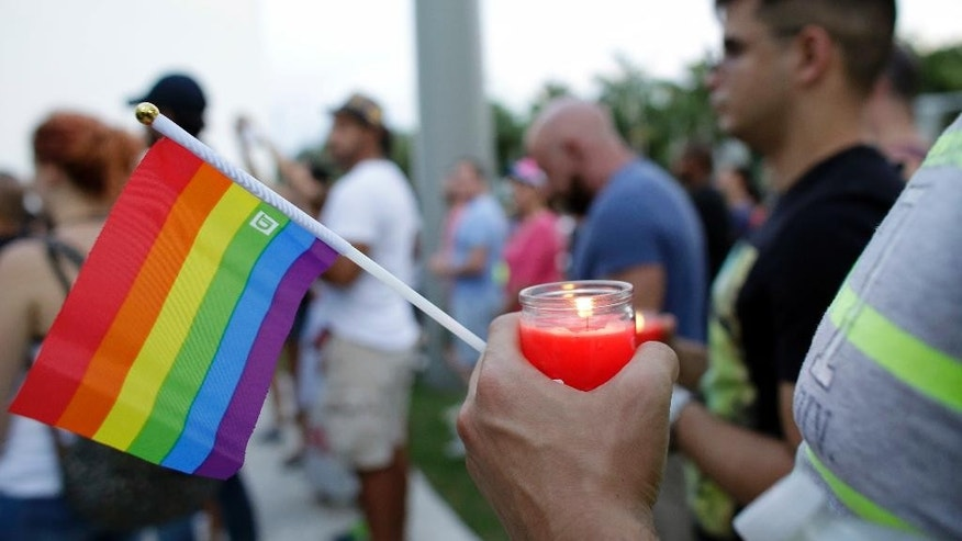 A man holds a candle and a rainbow flag during a vigil in memory of the victims of the Orlando mass shooting, Sunday, June 12, 2016, in Miami Beach, Fla.A gunman opened fire inside a crowded gay nightclub early Sunday, before dying in a gunfight with SWAT officers, police said. (AP Photo/Lynne Sladky)