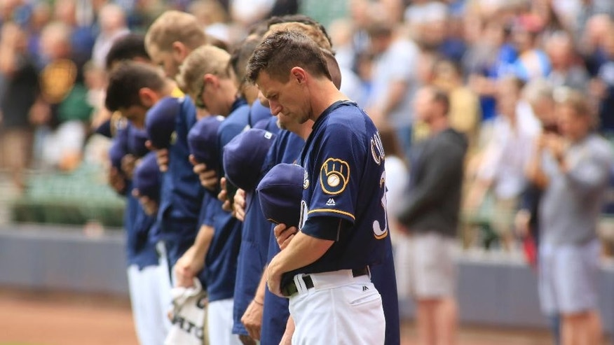 Members of the Milwaukee Brewers take a moment of silence for the victims of a mass shooting in Orlando, Fla., before a baseball game against the New York Mets, Sunday, June 12, 2016, in Milwaukee. (AP Photo/Darren Hauck)