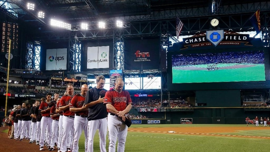 Arizona Diamondbacks manager Chip Hale, right, hitting coach Dave Magadan, second from right, pitching coach Mike Butcher, third from right, and bench coach Glenn Sherlock, fourth from right, join other Diamondbacks coaches and players for a moment of silence for the Orlando, Fla., mass shooting victims prior to a baseball game against the Miami Marlins, Sunday, June 12, 2016, in Phoenix. (AP Photo/Ross D. Franklin)
