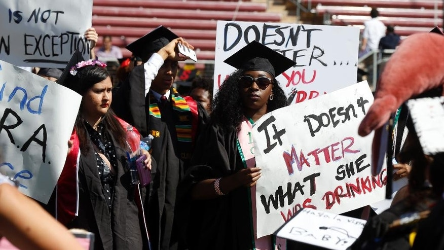 Protesters demonstrate during Stanford University graduation exercises at Stanford Stadium, Sunday, June 12, 2016, in Stanford, Calif. A group of women's rights advocates are urging a California agency to take action against the judge who sentenced a former Stanford University swimmer to six months in jail for sexually assaulting an unconscious woman. (AP Photo/D. Ross Cameron)
