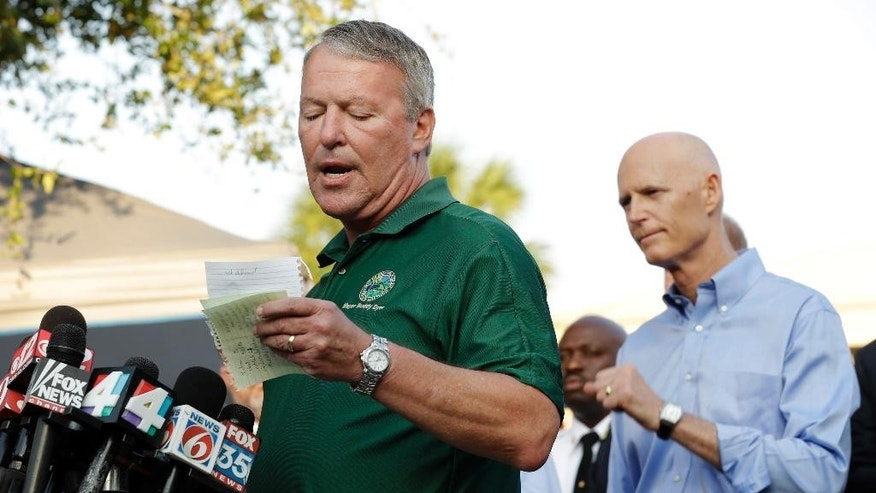 Orlando, Fla., Mayor Buddy Dyer reads details of the fatal shootings at Pulse Orlando nightclub during a media briefing Monday, June 13, 2016, in Orlando, Fla. Looking on is Florida Gov. Rick Scott at right. (AP Photo/Chris O'Meara)