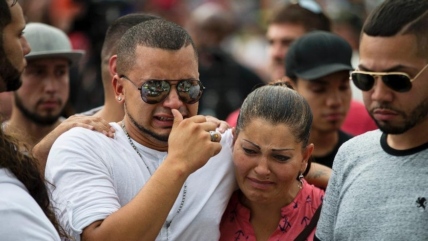 Victor Baez, left, cries with Iris Febo, as they mourn the loss of their friends Amanda Alvear and Mercedez Flores who were killed in the mass shooting at the Pulse nightclub, as they visit a makeshift memorial, Monday, June 13, 2016, in Orlando, Fla. A gunman killed dozens of people in a massacre at a crowded gay nightclub in Orlando on Sunday, making it the deadliest mass shooting in modern U.S. history. (AP Photo/David Goldman)