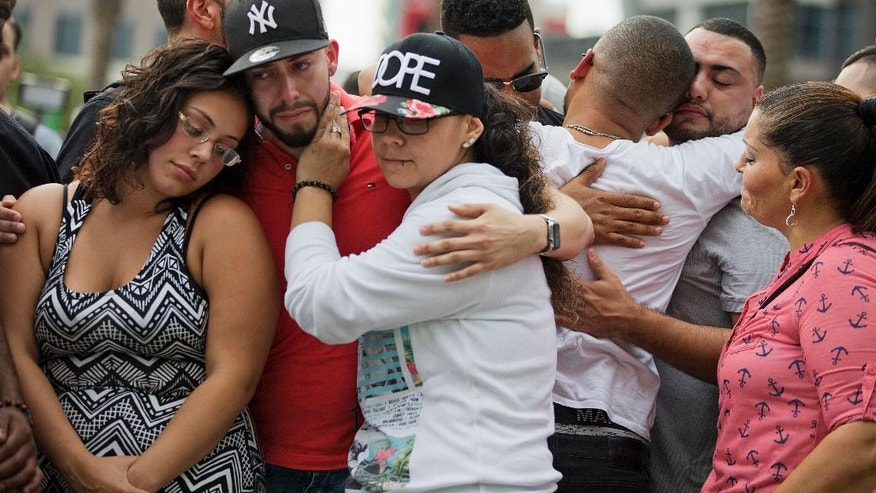 Mourners console each other as they grieve the loss of their friends Amanda Alvear and Mercedez Flores who were killed in the mass shooting at the Pulse nightclub, as they visit a makeshift memorial downtown, Monday, June 13, 2016, in Orlando, Fla. A gunman killed dozens of people in a massacre at a crowded gay nightclub in Orlando on Sunday, making it the deadliest mass shooting in modern U.S. history. (AP Photo/David Goldman)