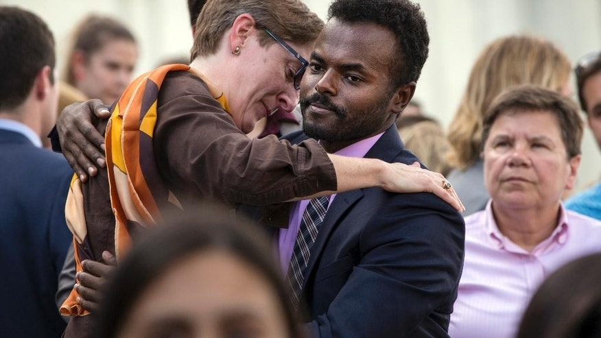 People comfort each other as members of the LGBT Congressional Staff Association and the Congressional Muslim Staff Association gather for a prayer and moment of silence on the steps of the Capitol to stand in solidarity with the Orlando community and to remember the victims of Sunday's shooting at an LGBT night club, in Washington, Monday, June 13, 2016. (AP Photo/J. Scott Applewhite)