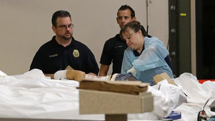 A medical worker examines a body at the Orlando Medical Examiner's Office , Sunday, June 12, 2016, in Orlando, Fla. A gunman opened fire inside a crowded gay nightclub early Sunday, before dying in a gunfight with SWAT officers, police said. (AP Photo/Alan Diaz)