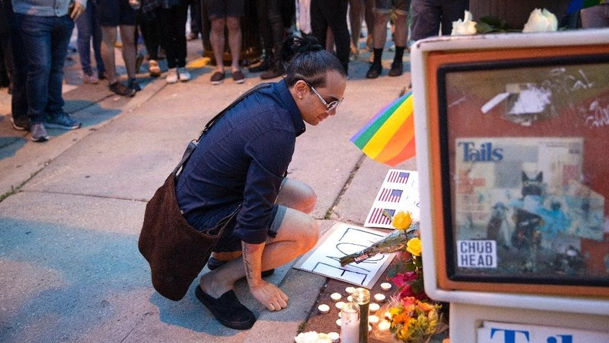 David Sotomayor, who is the cousin of Edward Sotomayor was among the victims, kneels at a makeshift memorial during a vigil for the victims of the Orlando nightclub shooting on Sunday, June 12, 2016, in the Boystown neighborhood of Chicago. (Erin Hooley/Chicago Tribune via AP)