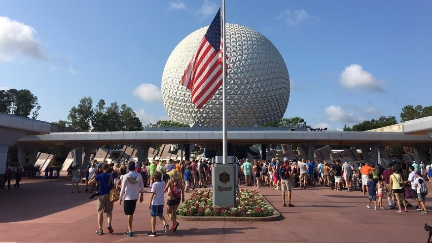 Tourists walk past a flag flown at half-mast in Epcot in Orlando on Monday, June 13, 2016. (Dewayne Bevil/Orlando Sentinel via AP) (Jacob Langston/Orlando Sentinel via AP)  MAGS OUT; NO SALES; MANDATORY CREDIT
