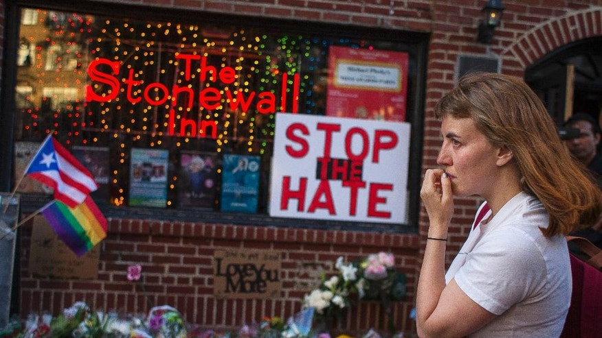 A woman cries and holds flowers in front of a makeshift memorial to remember the victims of a mass shooting in Orlando, Fla., in New York, Sunday, June 12, 2016. A gunman opened fire inside a crowded gay nightclub early Sunday before dying in a gunfight with SWAT officers. (AP Photo/Andres Kudacki)