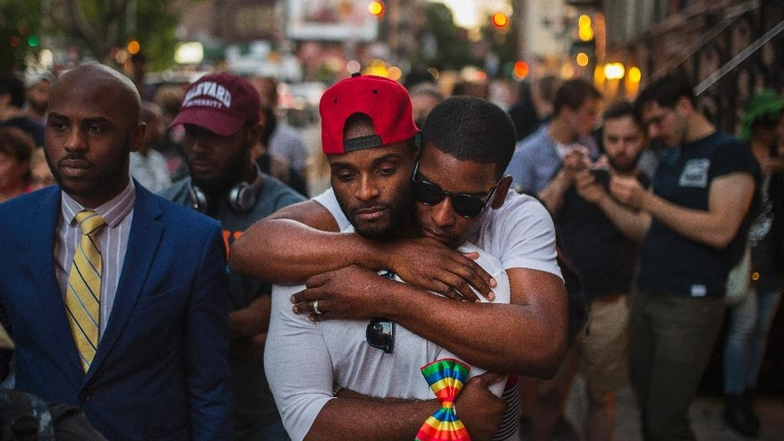 A couple embraces as people gather in front of a makeshift memorial in New York to remember the victims of a mass shooting in Orlando, Fla., Sunday, June 12, 2016.  A gunman opened fire inside a crowded gay nightclub early Sunday before dying in a gunfight with SWAT officers. (AP Photo/Andres Kudacki)