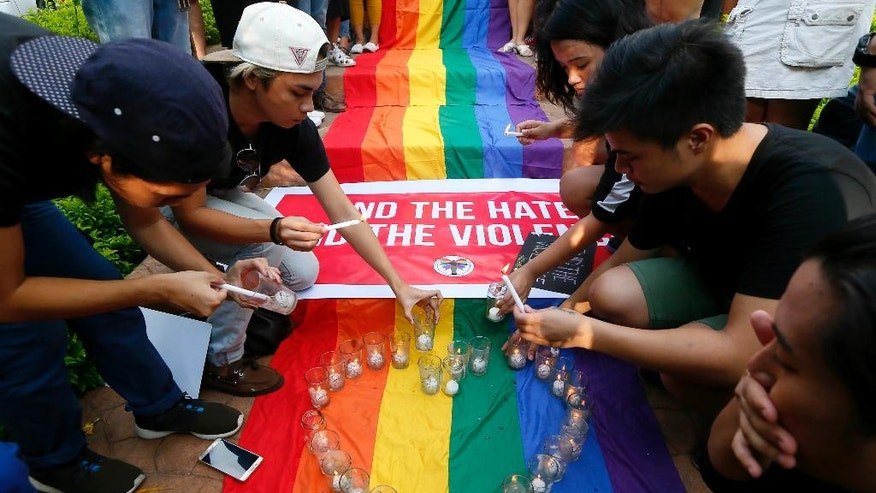 Filipino members of the LGBT (Lesbians Gays Bisexuals Transgenders) community light candles during a vigil to pay tribute to the victims of the Orlando, Fla. mass shooting Tuesday, June 14, 2016 at the University of the Philippines campus in suburban Quezon city northeast of Manila, Philippines. A gunman, later identified as Omar Mateen, opened fire inside a crowded gay nightclub in Orlando, Fla. early Sunday before dying in a gunfight with responding SWAT officers, authorities said.(AP Photo/Bullit Marquez)