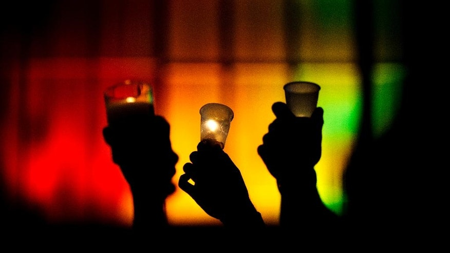 People hold up candles against a rainbow lit backdrop during a vigil for those killed in a mass shooting at the Pulse nightclub downtown Monday, June 13, 2016, in Orlando, Fla. A gunman has killed dozens of people in a massacre at a crowded gay nightclub in Orlando on Sunday, making it the deadliest mass shooting in modern U.S. history. (AP Photo/David Goldman)
