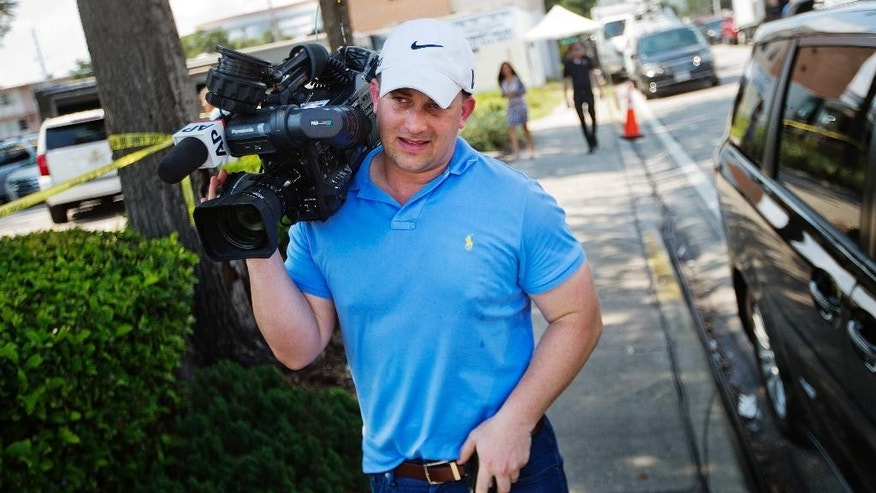 Associated Press video journalist Josh Replogle works the scene near a mass shooting at the Pulse nightclub Tuesday, June 14, 2016, in Orlando, Fla. Replogle helped put himself through college by working at the Pulse dance club for two years. He returned this week to cover the mass shooting at the club. (AP Photo/David Goldman)