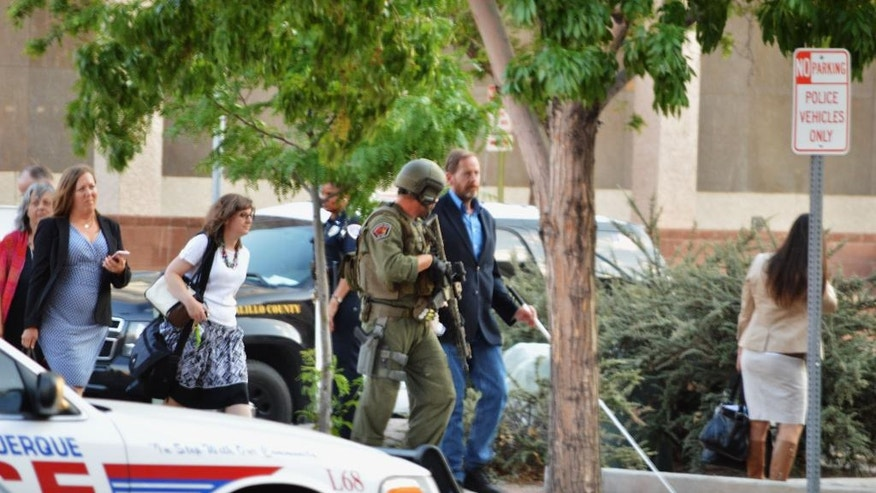 "Albuquerque police in tactical gear escort out Albuquerque, N.M., City Hall employees on Monday, June 13, 2016, after receiving reports of a possible active shooter and hostage situation in the city building. Albuquerque police spokesman Tanner Tixier said one man was being detained and investigators believed that person was ""the initiator"" who spurred calls from employees inside the building. olice believe the situation may have been the result of a hoax, but they were not taking any chances. (AP Photo/Russell Contreras)"