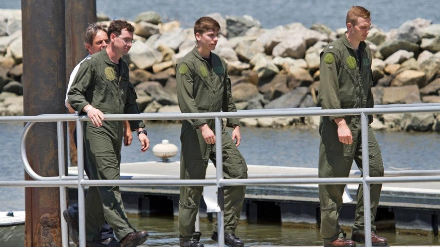 Three passengers that were aboard a Navy helicopter that crashed into the James River walk off a boat ramp after being rescued uninjured, at Huntington Park Tuesday, June 14, 2016, in Newport News, Va. (Joe Fudge/The Daily Press via AP) MANDATORY CREDIT