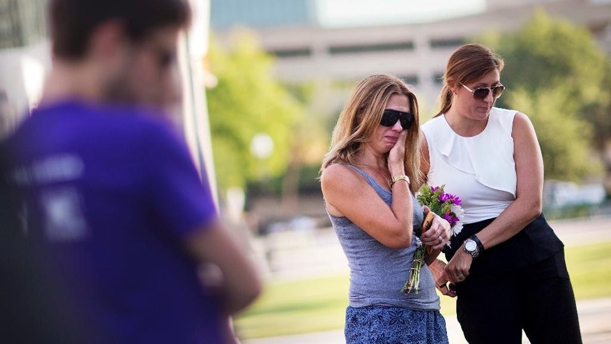 Amy Semesco, left, wipes a tear, while visiting a makeshift memorial for the victims of a mass shooting at the Pulse nightclub with Bree Balchunas on Tuesday, June 14, 2016, in Orlando, Fla. (AP Photo/David Goldman)