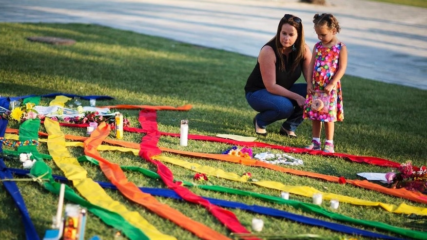 Rhonda Rodeffer, left, and her daughter Kennedy, 4, visit a makeshift memorial for the victims of a mass shooting at the Pulse nightclub Tuesday, June 14, 2016, in Orlando, Fla. (AP Photo/David Goldman)