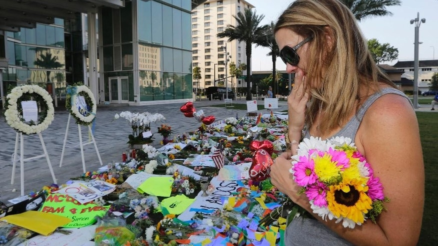 Amy Semesco wipes a tear as she pays tribute, Tuesday, June 14, 2016, in Orlando, Fla., at a growing memorial at the The Dr. Phillips Center for the victims of the mass shooting Sunday at the Pulse Nightclub. (AP Photo/Alan Diaz)