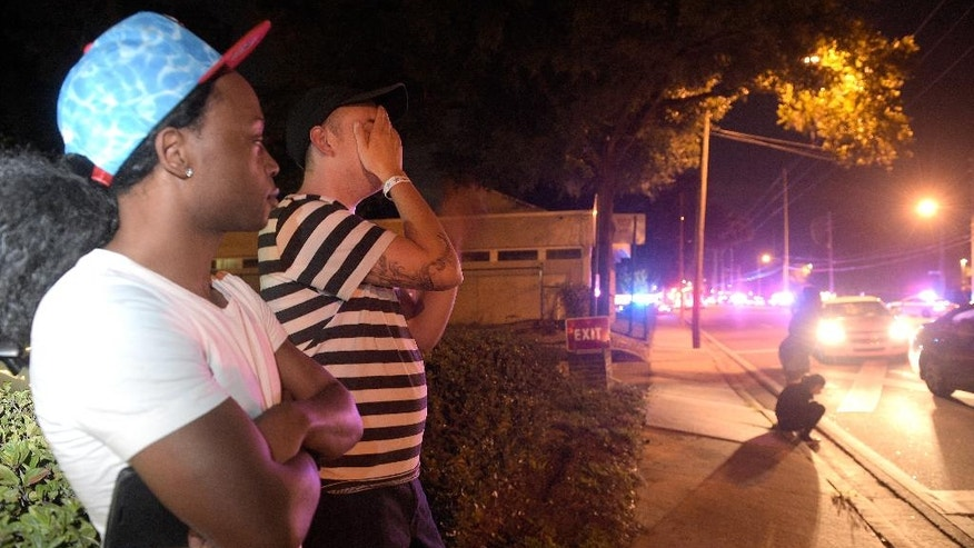 FILE - In this June 12, 2016 file photo, Jermaine Towns, left, and Brandon Shuford wait down the street from Pulse nightclub where a gunman opened fire in Orlando, Fla., Sunday, June 12, 2016. Towns said his brother was in the club at the time.  (AP Photo/Phelan M. Ebenhack, File)