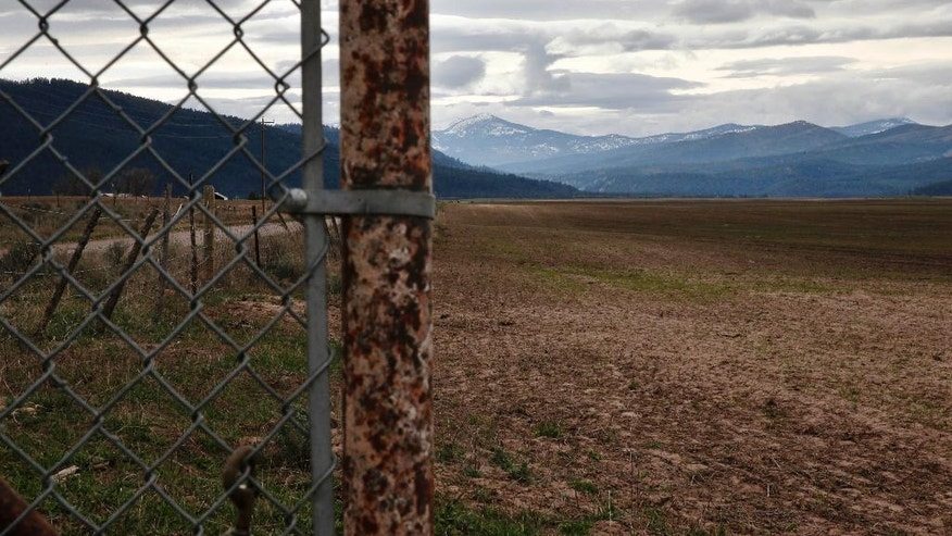 """In this April 12, 2016 photo, mountains rise behind a fence on land belonging to Gloria Roark, a vocal opponent of refugees coming to her state, near Clearwater, Mont. What started as a disagreement over whether to welcome dozens of refugees to this corner of western Montana soon erupted into something much larger, encompassing wildly divergent views of Islam, big government and whether Americans should """"take care of our own"""" before worrying about newcomers. (AP Photo/Brennan Linsley)"""