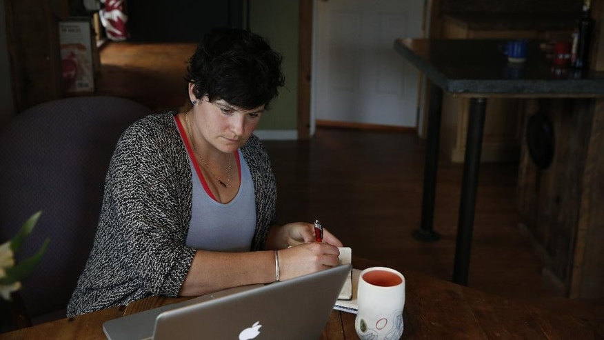 """In this April 14, 2016 photo, activist and Soft Landing founder Mary Poole works at home in Missoula, Mont. Haunted by the 2015 photo of a Syrian refugee boy washed ashore in Turkey, she and members of her book group asked: Why not bring a small number of Syrian families to Missoula? """"It wasn't even a grain of sand in my brain that people wouldn't want to help starving, drowning families. I didn't do this to be controversial. I didn't do this to stir the pot,"""" she says. (AP Photo/Brennan Linsley)"""