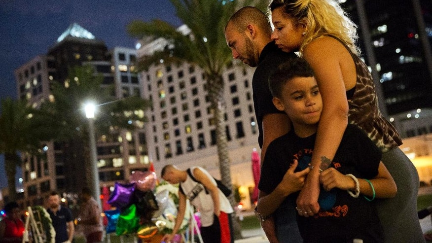 Jennifer Johnson, right, leans on her boyfriend Jeansem Sambolin while standing with her son Tyrone Clarke, 8, as they visit a makeshift memorial for the victims of the mass shooting at the Pulse Orlando nightclub Tuesday, June 14, 2016, in Orlando, Fla. Franky Jimmy Dejesus Velazquez was one of those killed and had worked with Johnson. (AP Photo/David Goldman)
