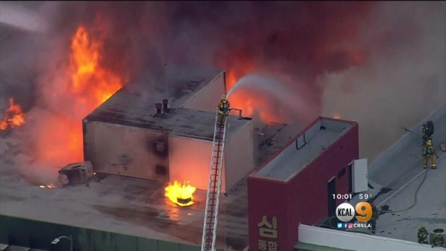 This Monday, June 13, 2016 image from video provided by KCBS-TV/KCAL-TV shows Los Angeles firefighters battling a blaze in an abandoned two-story office building in the city's Westlake District. Authorities say the death toll has risen to several people a day after the fire in the office building near downtown Los Angeles. (KCBS-TV/KCAL-TV via AP) MANDATORY CREDIT