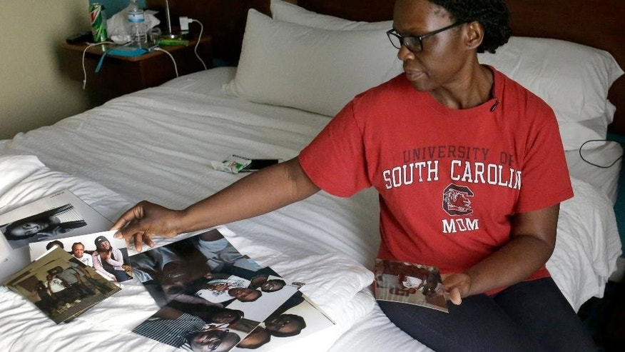 In this Wednesday, June 15, 2016 photo, Andrea Drayton looks over family photos that show her daughter, Deonka Drayton, a victim of the recent mass shootings at the Pulse nightclub in Orlando, Fla. Drayton, her husband, Shepherd, son, Shepherd III, and daughter, Alexia, piled in the family car and began an excruciating early morning journey south from South Carolina to Orlando, where a gunman had opened fire at a gay nightclub killing 49 and wounding scores of others before being killed by police. (AP Photo/John Raoux)
