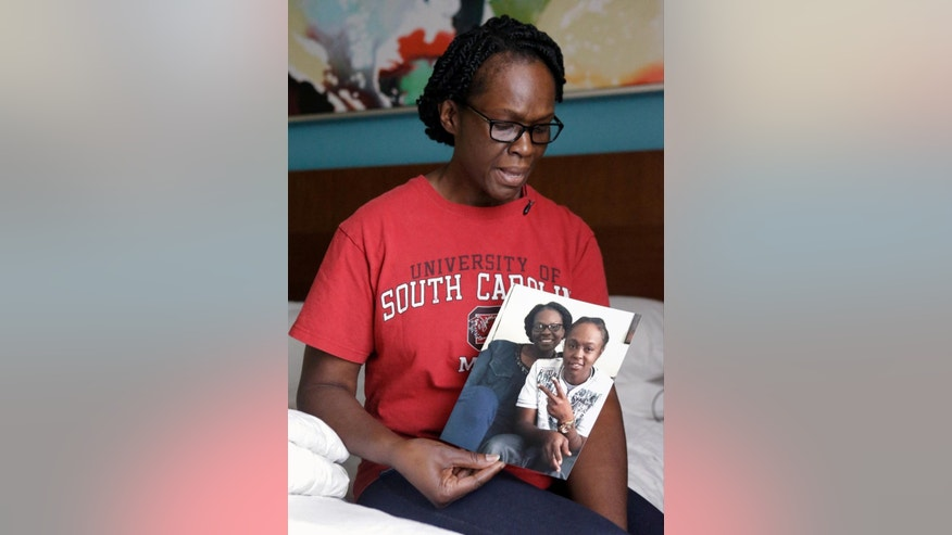 In this Wednesday, June 15, 2016 photo, Andrea Drayton holds a family photo of her and her daughter Deonka Drayton, a victim of the recent mass shootings at the Pulse nightclub in Orlando, Fla. Drayton, her husband, Shepherd, son, Shepherd III, and daughter, Alexia, piled in the family car and began an excruciating early morning journey south from South Carolina to Orlando, where a gunman had opened fire at a gay nightclub killing 49 and wounding scores of others before being killed by police. (AP Photo/John Raoux)