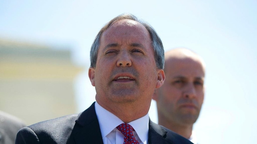 File - In this April 18, 2016, file photo, Texas Attorney General Ken Paxton meet with members of the media at the Supreme Court in Washington. A federal judge has dismissed a lawsuit that Texas brought against the federal government in hopes of halting the arrival of Syrian refugees. (AP Photo/Pablo Martinez Monsivais, File)