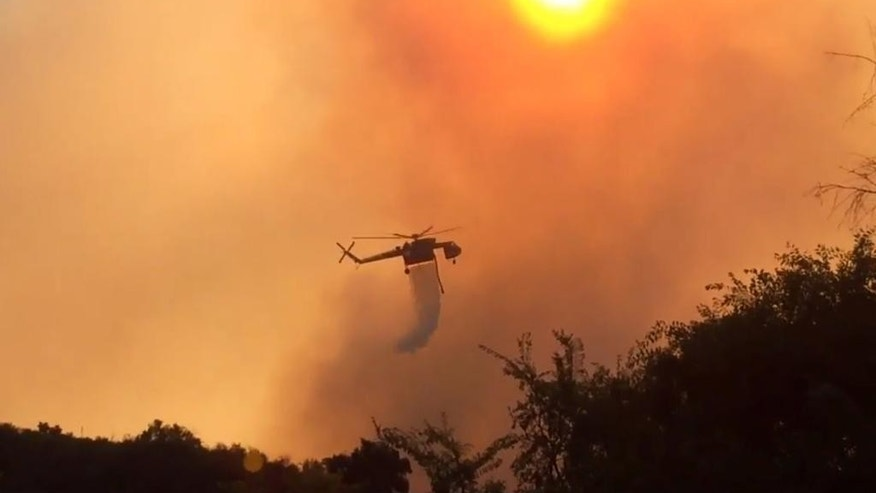 In this image made from video, a helicopter makes a water drop over a wildfire in a remote coastal area west of Santa Barbara, Calif., on Thursday, June 16, 2016. A fleet of aircraft dropped water and retardant to combat a wind-driven wildfire burning out of control Thursday. (KABC-7 via AP) MANDATORY CREDIT