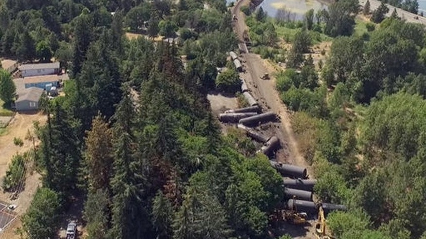 This video image taken from a drone shows an aerial view of crumpled oil tankers lying beside the railroad tracks after a fiery train derailment on June 3 prompted evacuations from the tiny Columbia River Gorge town about 70 miles east of Portland, on Monday, June 6, 2016, in Mosier, Ore.