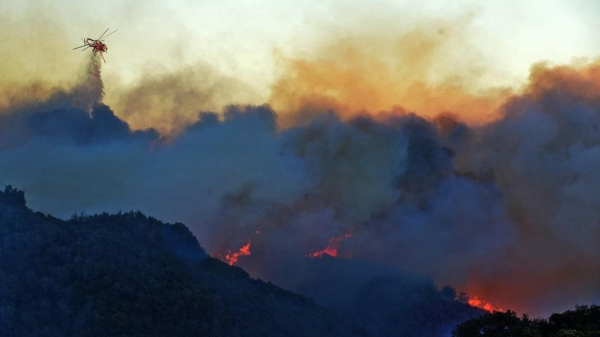 In this Wednesday evening, June 15, 2016 photo provided by the Santa Barbara County Fire Department, a helicopter makes a water drop on flames from the Shirpa Fire in Santa Barbara County west of Goleta, Calif. The wildfire burning in rugged coastal canyons west of Santa Barbara is growing as it feeds on vegetation that hasn't burned in 70 years. (Mike Eliason/Santa Barbara County Fire Department via AP)
