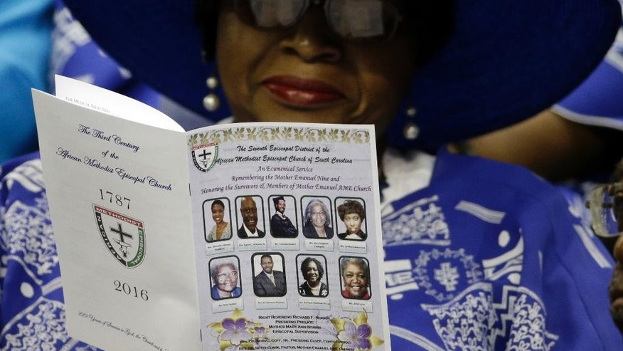 A woman reads the program for a memorial service honoring those killed in last year's shooting at the Mother Emanuel AME Church in Charleston, S.C., Friday, June 17, 2016. Friday marks one year since nine people were shot and killed while studying their Bibles in a basement room at the historic church.  (AP Photo/Chuck Burton)
