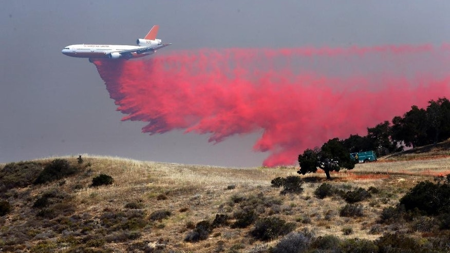 "A DC-10 tanker drops fire retardant at a low altitude to help combat a wildfire near Santa Barbara, Calif. on Friday, June 17, 2016. The latest size estimate Friday morning is nearly three times the previous acreage, with just 5 percent containment. The fire has been stoked by the region's afternoon and evening ""Sundowner"" winds, which blast down the face of the Santa Ynez Mountains toward the Pacific Ocean. (AP Photo/Nick Ut)"