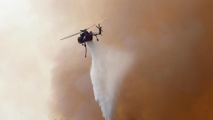 A firefighting helicopter makes a water drop to help combat a wildfire near Santa Barbara, Calif., on Friday, June 17, 2016. Stoked by winds, a wildfire burning west of Santa Barbara roared down mountain slopes toward the Pacific Ocean, shutting down California's major coastal highway and forcing a group of firefighters to seek shelter behind a fire engine as flames licked at them. (AP Photo/Nick Ut)