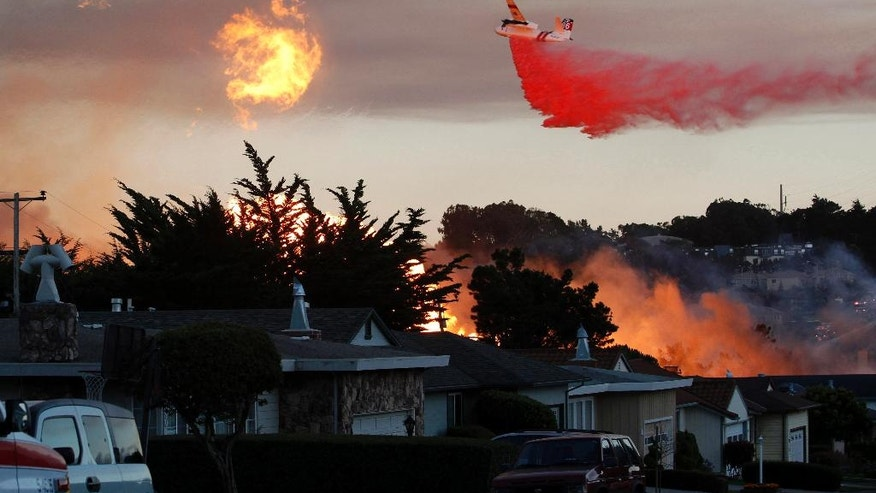 FILE - In this Sept. 9, 2010, file photo, a massive fire following a pipeline explosion roars through a mostly residential neighborhood in San Bruno, Calif. One of the country's largest utility companies is set to face a jury in a criminal trial accusing it of misleading investigators in the wake of a deadly pipeline explosion in the San Francisco Bay Area. The September 2010 blast of a Pacific Gas & Electric Co. natural gas pipeline sent a giant plume of fire into the air in a neighborhood in San Bruno, killing eight people and destroying 38 homes. Opening arguments in the trial began Thursday, June 16, 2016. (AP Photo/Jeff Chiu, File)