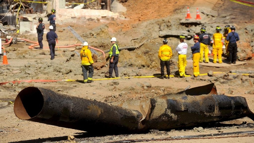 FILE - In this Sept. 11, 2010, file photo, a natural gas line lies broken on a San Bruno, Calif., road after a massive explosion. One of the country's largest utility companies is set to face a jury in a criminal trial accusing it of misleading investigators in the wake of a deadly pipeline explosion in the San Francisco Bay Area. The September 2010 blast of a Pacific Gas & Electric Co. natural gas pipeline sent a giant plume of fire into the air in a neighborhood in San Bruno, killing eight people and destroying 38 homes. Opening arguments in the trial began Thursday, June 16, 2016. (AP Photo/Noah Berger, File)