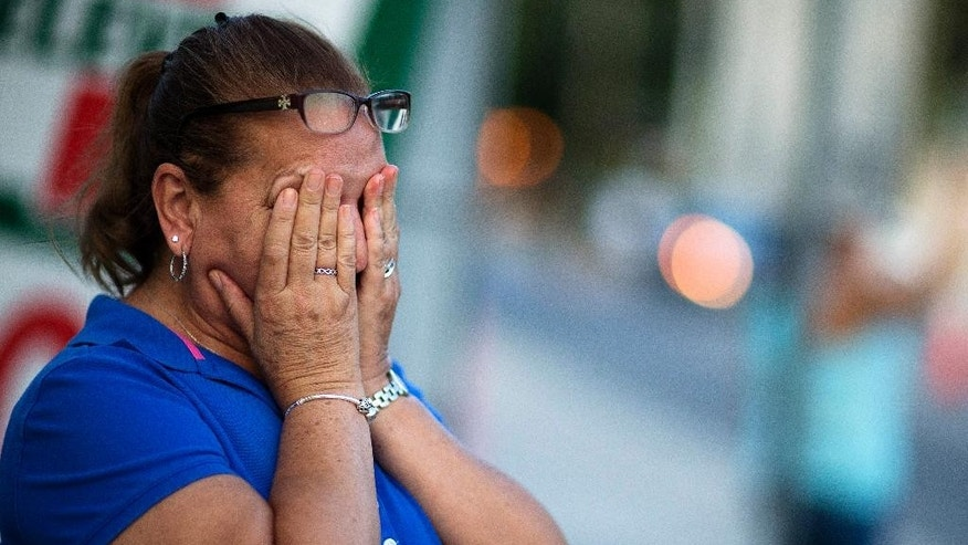 Carmen Feldman, of Orlando, cries while visiting for the first the scene of the Pulse nightclub mass shooting from a block away Friday, June 17, 2016, in Orlando, Fla. (AP Photo/David Goldman)