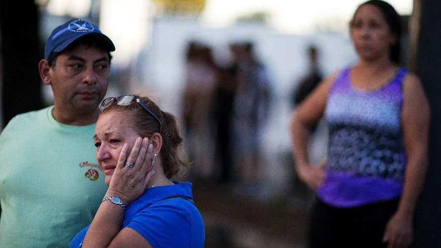 Carmen Feldman, of Orlando, right, cries while visiting for the first the scene of the Pulse nightclub mass shooting from a block away with Jose Garcia, left, Friday, June 17, 2016, in Orlando, Fla. (AP Photo/David Goldman)