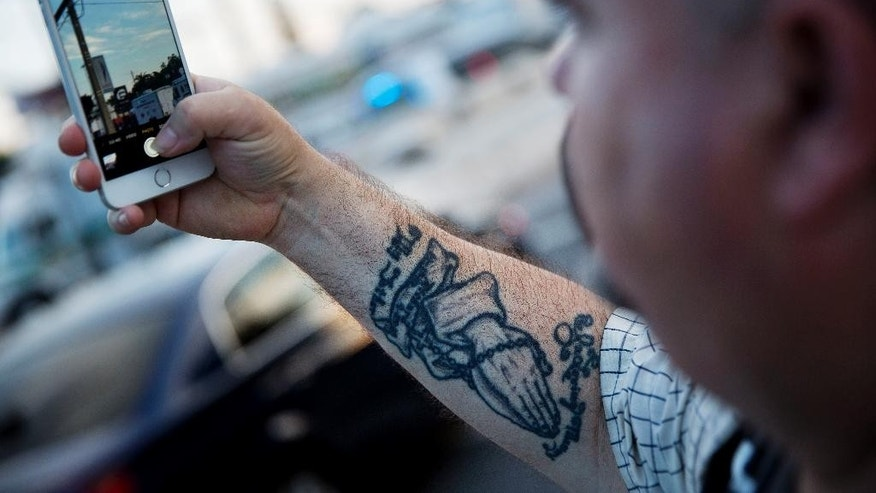 A tattoo of hands clasped in prayer decorate the arm of Dennis Buscemi, of Orlando, as he takes a picture of the scene of the Pulse nightclub mass shooting from a block away Friday, June 17, 2016, in Orlando, Fla. (AP Photo/David Goldman)