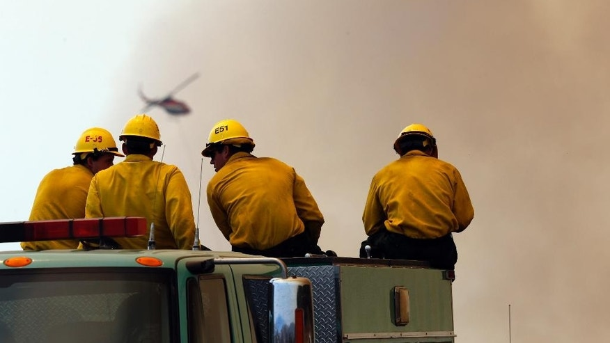 "Firefighters watch as a helicopter makes a water drop over a wildfire near Santa Barbara, Calif., on Friday, June 17, 2016. The latest size estimate Friday morning is nearly three times the previous acreage, with just 5 percent containment. The fire has been stoked by the region's afternoon and evening ""Sundowner"" winds, which blast down the face of the Santa Ynez Mountains toward the Pacific Ocean. (AP Photo/Nick Ut)"
