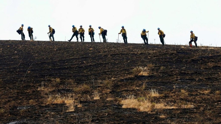 Santa Barbara firefighters work the crest of a ridge after a wildfire burned the hill west of Goleta, Calif., Friday, June 17, 2016. Stoked by winds, a wildfire burning west of Santa Barbara roared down mountain slopes toward the Pacific Ocean, shutting down California's major coastal highway and forcing a group of firefighters to seek shelter behind a fire engine as flames licked at them. (AP Photo/Nick Ut)