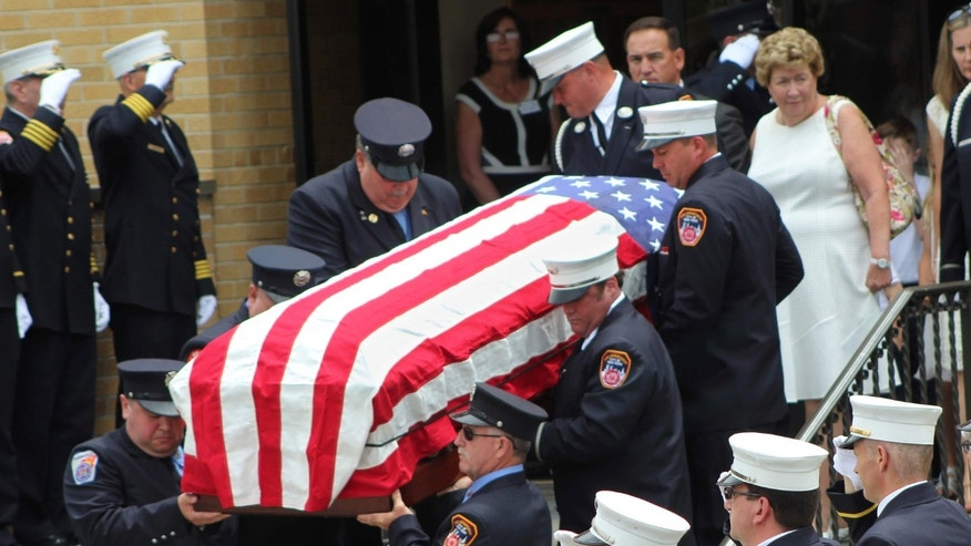 June 17, 2016: The flag-draped casket of New York Fire Department Battalion Chief Lawrence Stack is carried out of his funeral in St. James, N.Y