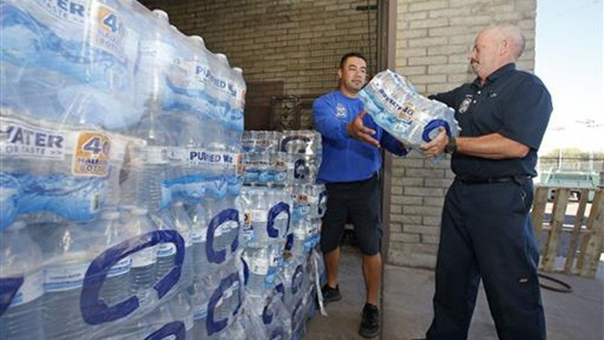 Glendale Fire Department firefighter Chris Greene, right, gets a case of water from service worker Edi Marroquin, left, from the dozens of cases of water at the Glendale Fire Department Resource Center as they prepare for the record-setting heat predicted for the weekend Thursday, June 16, 2016, in Glendale, Ariz. (Associated Press)